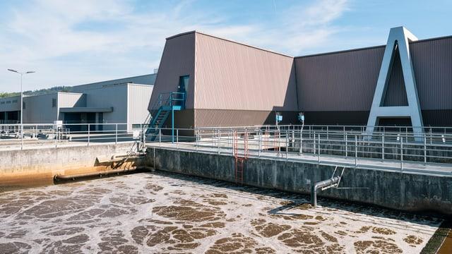 Ein Klärwerk, im Vordergrund ein Becken dreckiges Wasser und hinten ein kantiges Gebäude.