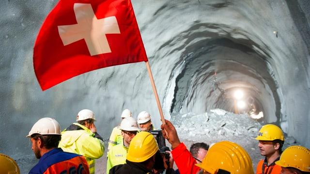 Bauarbeiter mit Helm schwenken eine Schweizer Flagge in einem Tunnel.
