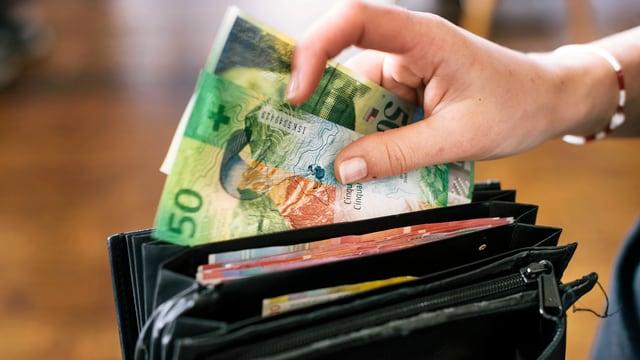 Eine Person entnimmt einem Serviceportemonnaie zwei 50er-Noten.