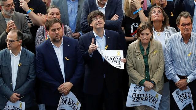 Männer und Frauen stehen in einer Menge, Puigdemont mit Brille blickt nach oben.