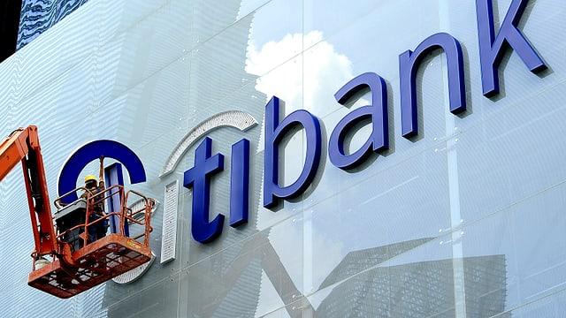 Glänzende Fassade einer Citibank-Filiale. Die Glasfassade wird von einer Hebebühne aus gereinigt.