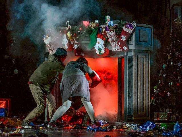 Hänsel und Gretel von hinten, viel Rauch und viele Geschenke auf der Bühne des Opernhauses.