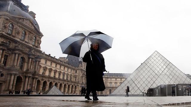 Frau mit Regenschirm steht vor dem Louvre.