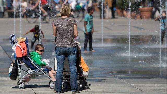 Eine Frau mit Kinderwagen steht auf dem Bundesplatz beim Brunnen.