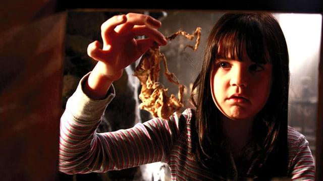 Ein Mädchen hält einen Haufen Würmer in der Hand.
