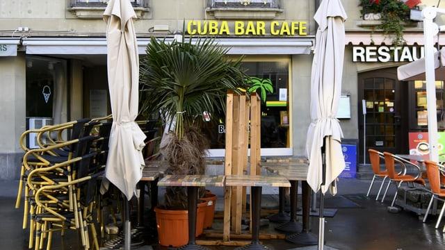 Zusammengestellte Stühle und Tische vor der geschlossenen Cuba Bar.