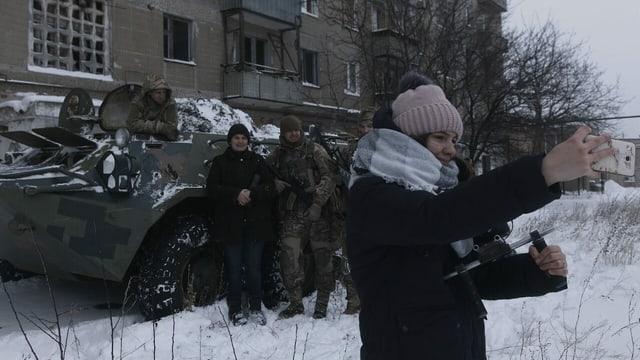 Ein Mädchen steht vor einem Panzer mit Soldaten und filmt sich dabei selbst.