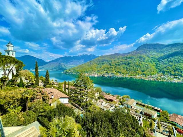 Blick vom Hang auf blauen See mit viel Grün und blauem Himmel mit wenigen Wolken