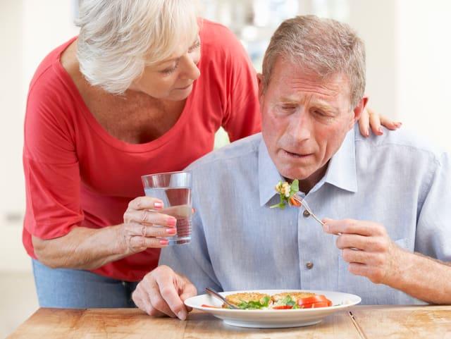 Alte Frau kümmert sich um alten Mann.