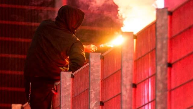 Hooligan zündet eine Fackel.