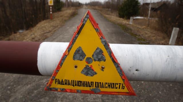 Eine Absperrung mit dem Symbol für Radioaktivität am Rande der Sperrzone in Tschernobyl.