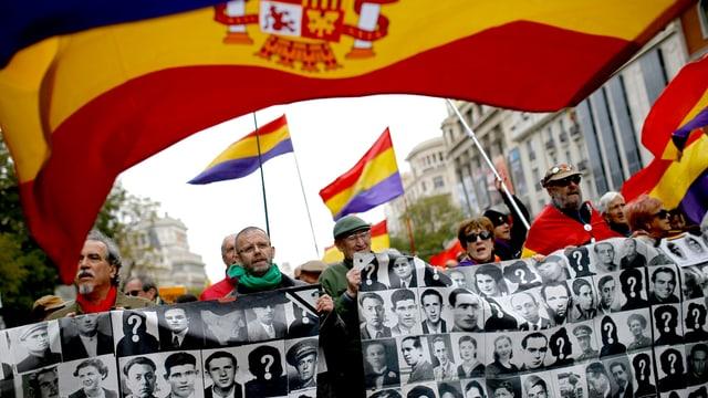Menschen an einer Demonstration, sie halten ein Banner mit Porträts von Menschen, dazu spanische Nationalflaggen.