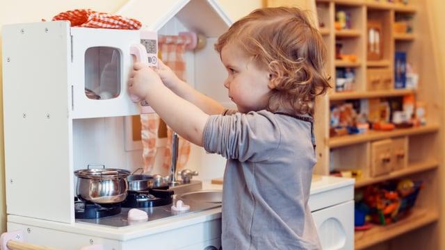 Ein Mädchen spielt mit einer Spielzeug-Kochnische.