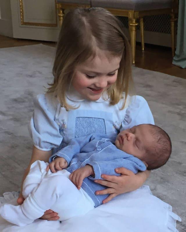 Prinzessin Estelle sitz in einem weiss-blauen Kleidchen am Boden und hält ihren Baby-bruder Oscar im Arm.