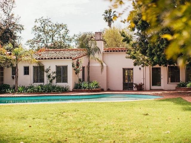Eine einstöchige Villa im spanischen Stil mit Pool umgeben von einem Garten.