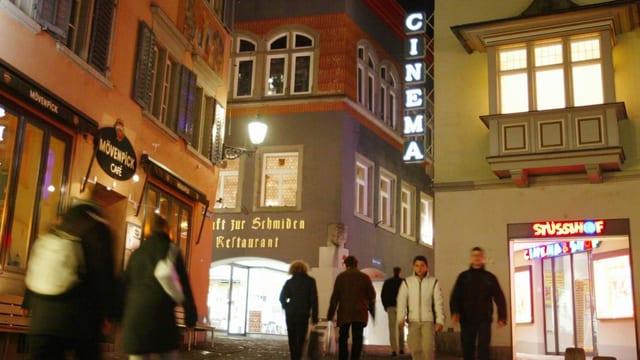 An einer Gasse in der Zürcher Altstadt steht das Kino Stüssihof. Es ist dunkel und die Leuchtschrift ist zu sehen.