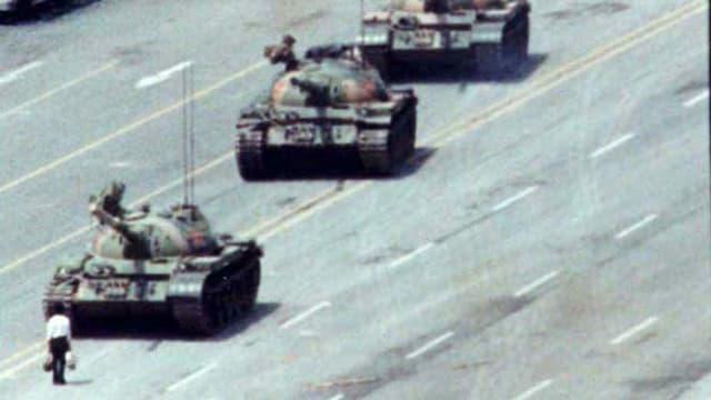 Eine Person steht vor einer Panzerkolonne.