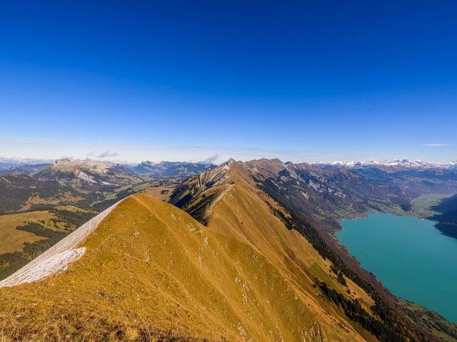 Rechts tief unten ein See, links noch etwas Schnee, in der Mitte ein schmaler Grat.