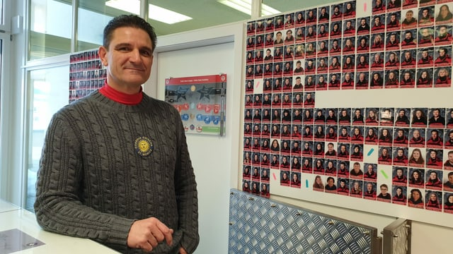 Bruno Marinoni davant la paraid cun las fotografias dals collavuraturs.
