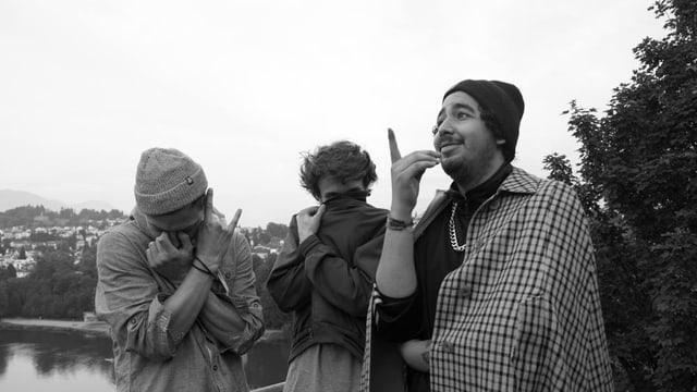 schwarzweissen Bild, drei Männer stehen vor Wald und See und verdecken ihre Gesichter.