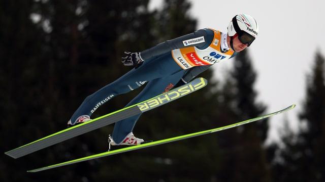 Simon Ammann springt mit seinen Skiern in V-Form.