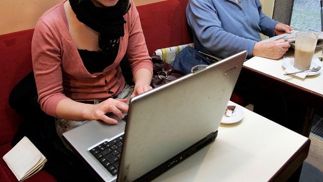 Eine junge Frau sitzt im Café am Laptop.