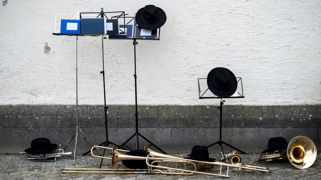 Vier Notenständer, schwarze Hüte und ein paar schwarze Hüte.