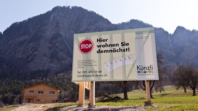 Ein Schild mit der Aufschrift «Hier bauen Sie demnächst» an einem sonnigen Hang.