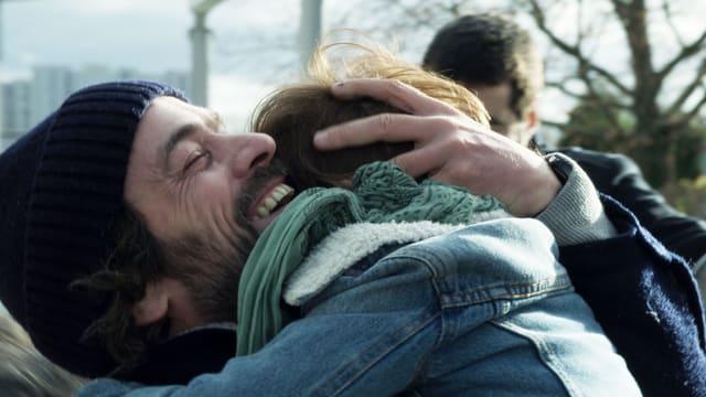 Mann umarmt Kind
