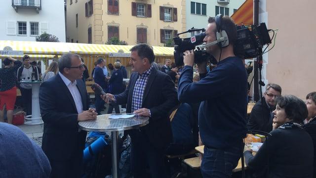 Kameramann und zwei Personen bei einem Interview.
