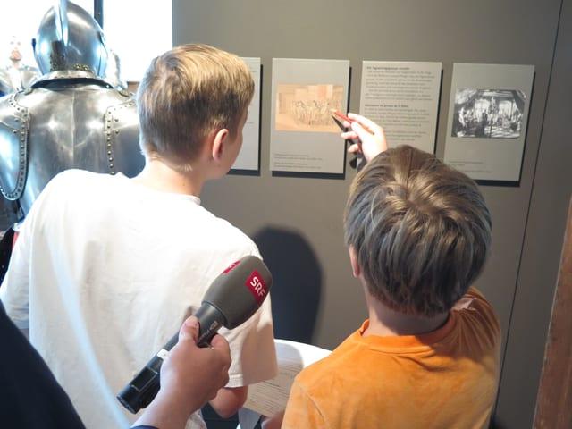 Zwei Buben diskutieren vor einer Tafel im Museum.
