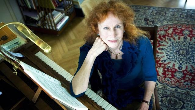 Blick von oben auf eine Frau, die ihren Ellbogen auf einem Klavier abstützt und direkt in die Kamera schaut.