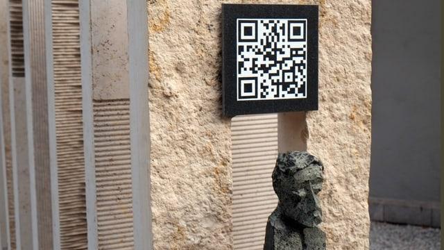 Ein Schild mit einem QR-Code auf einem Grabstein.