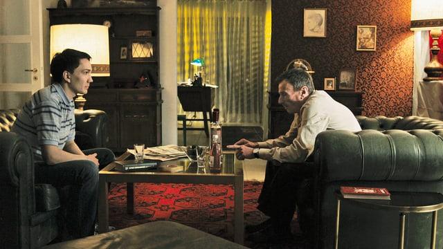 2 Männer sitzen im Wohnzimmer und reden miteinander