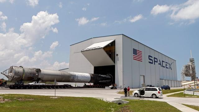 Eine geborgene Falcon-Rakete wird aus einem Hangar transportiert.