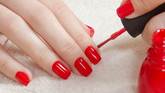 Frau lackiert sich rote Fingernägel.