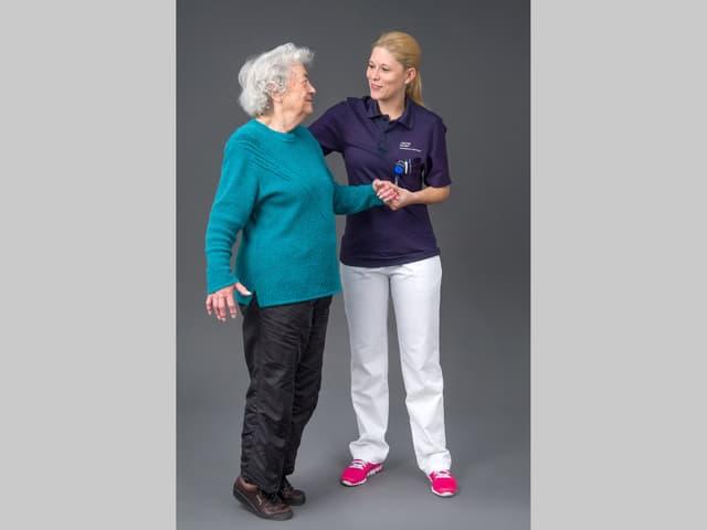Seniorin steht auf den Zehenspitzen und wird von einer jungen Frau gestützt