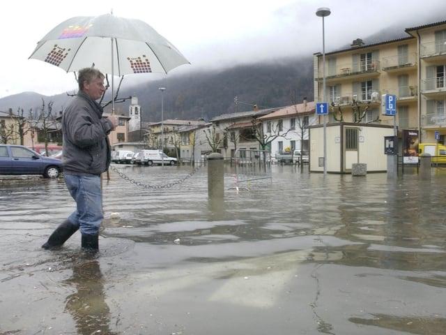 Mensch mit Schirm überquert einen überfluteten Parkplatz