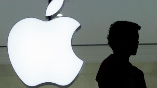 Ein Logo von Apple und der Schatten einer Person daneben.