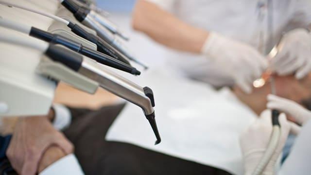 Zahnarztgeräte im Vordergrund, dahinter sieht man unscharf zahnärztliches Personal bei der Behandlung eines Patienten.