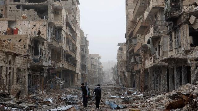 Menschen gehen durch eine zerstörte Strasse.