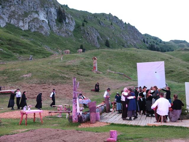 Freilichttheaterszene mit mehreren Menschen.