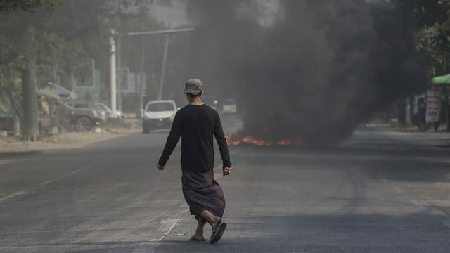 Mann läuft auf Strasse. Es brennt ein Feuer darauf. Viel Rauch.