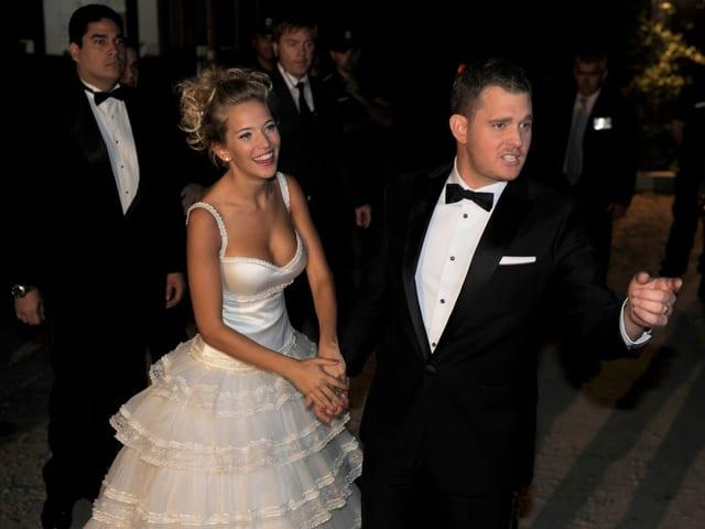 Blonde Frau in weissem Hochzeitskleid mit Mann in schwarzem Anzug