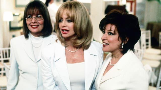 drei Frauen in weissen Anzügen lachen