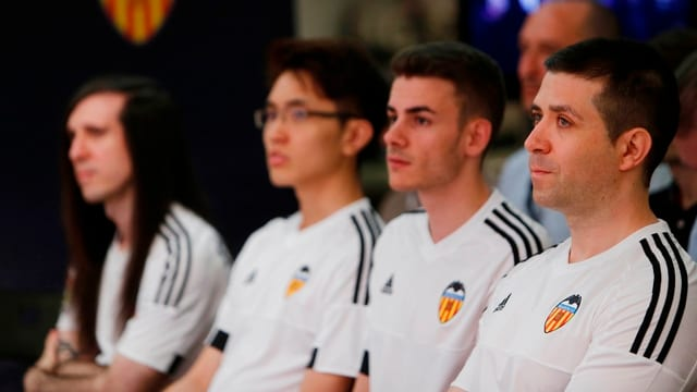 Vier junge Männer in Team-Trikots.