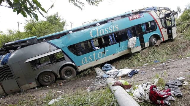 Ein Bus liegt in einem Abhang, teilweise sind Fenster zerbrochen und Kleider liegen herum.