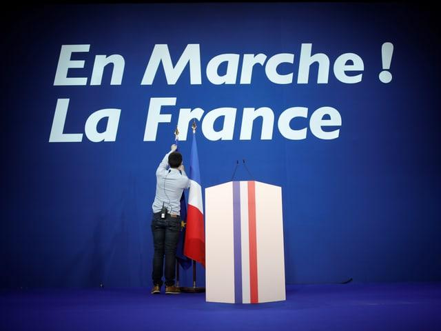 En Marche! Schriftzug vor Rednerpult und französischer Flagge.