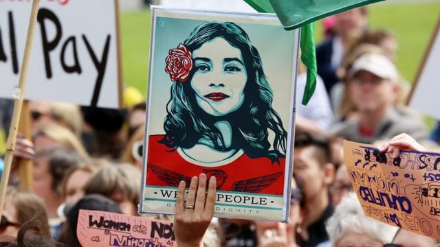 In einer Gruppe von Menschen hält eine Hand ein Plakat hoch. Es zeigt die Zeichnung einer Frau, die den betrachter stolz anblickt.