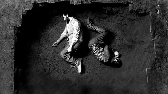 Zwei Männer liegen gekrümmt in einem Loch in der Erde.